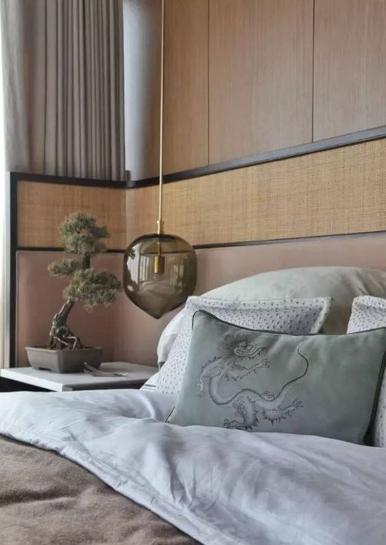 wooden wall, wooden headboard with pink layer on bottom hald, side table, glass hanging bedside lamp, brown bedding