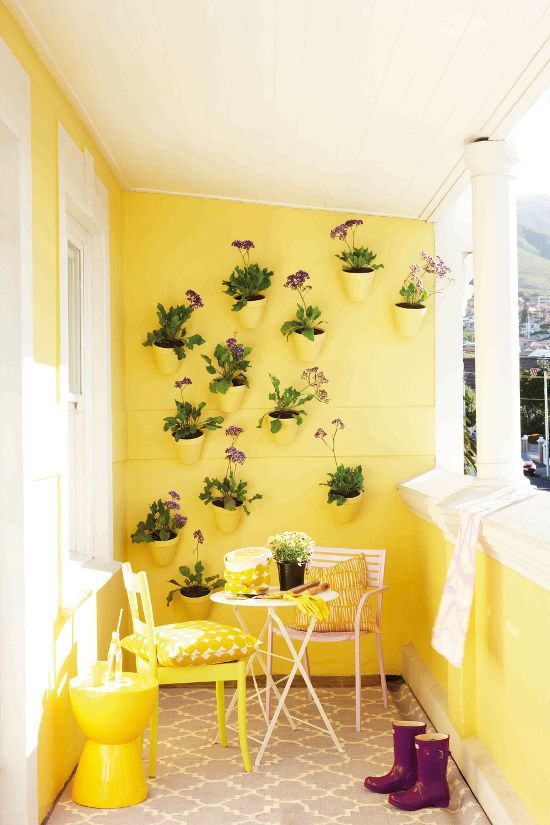 yellow balcony with yellow on wall, chair, stool, pillow, white chair, white table, white paint, yellow pots on the wall, grey rug