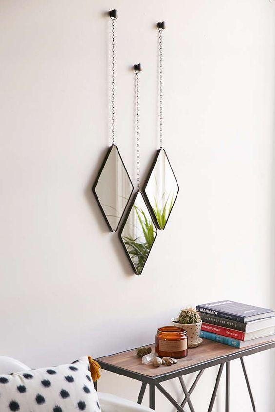 a set of three diamond mirror above wooden table