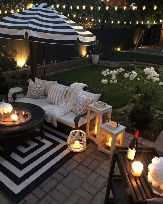 backyard corner with black whtie rug, black wooden round coffee table, wooden sofa with white cushions, pillows, striped big umbrella, black wooden shelevs
