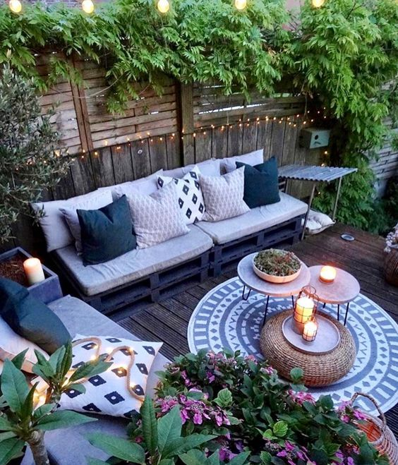 backyard corner, wooden floor, wooden fence, crate bench with cushion, pillows, nesting coffee tables, rattan ottoman