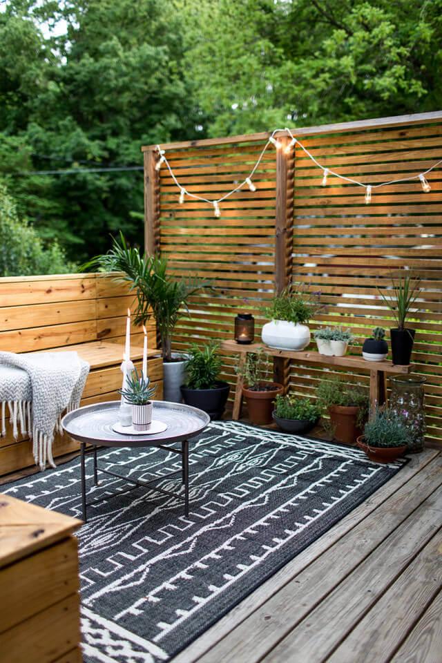backyard corner, wooden floor, wooden screen, wooden built in corner bench, wooden bench for plants, round coffee table