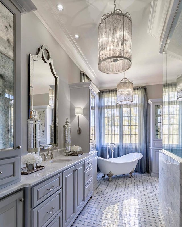 bathroom, basket weave floor tiles, light grey wooden cabinet, light grey wall, mirror, white wall tiles, white tub with legs, fringes pendants, sconces, marble vanity top