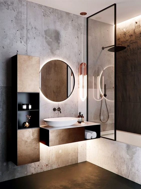 bathroom, dark copper look floor, light grey wall, tub, copper vanity with white roun sink, round mirror, copper cabinet with shelves, clear glass partition, black shower