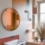 Bathroom, Different Colored Block On The Wall, White Sink, Round Mirror, Asymmetrical Pendant, Peach Cabinet Near The Window
