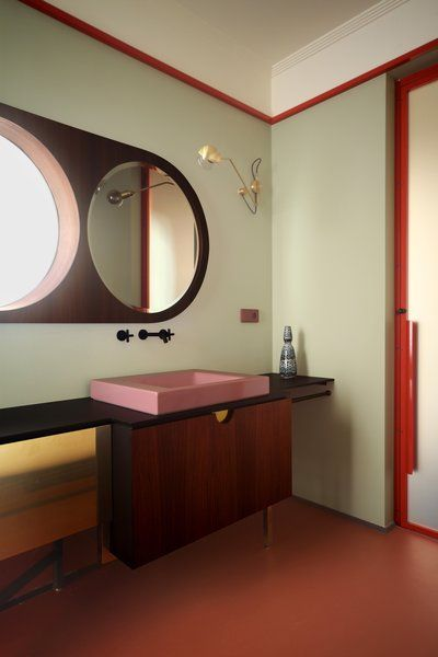 bathroom, pale green wall, red frame wall, round two mirrors in one, wooden vanity with black long top, pink sink, orange floor