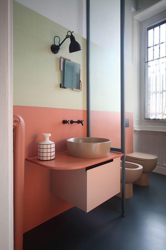 bathroom, pink green white painted wlal, pink floating asymetric vanit with grey sink, brown toilet, window, glass partition, black sconces
