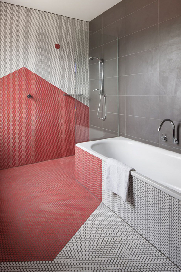 bathroom, tiny hexagon tiles in white and pink in great pattern on the floor, wall, tub, silver faucet, glass partition