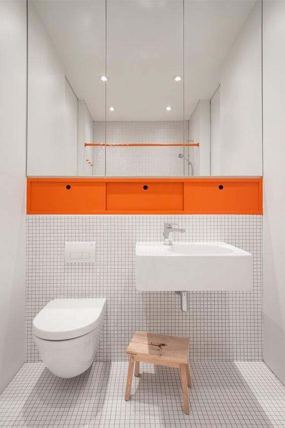 bathroom, white tiny square tiles ont he floor and half the wall, white floating sink, white toilet, orange middle drawers, tall mirror on the wall, wooden stool