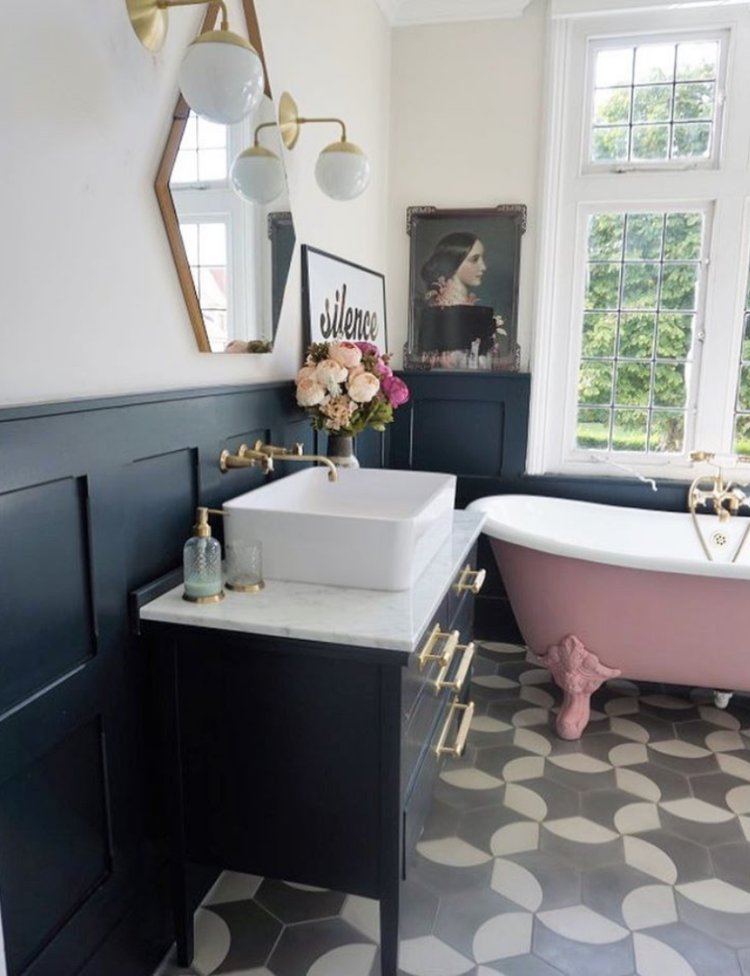 bathroom, white wall, black wainscoting, pink tub with claw foot, black cabinet white marble, white sink, hexagon mirror, sconce, patterned floor tiles