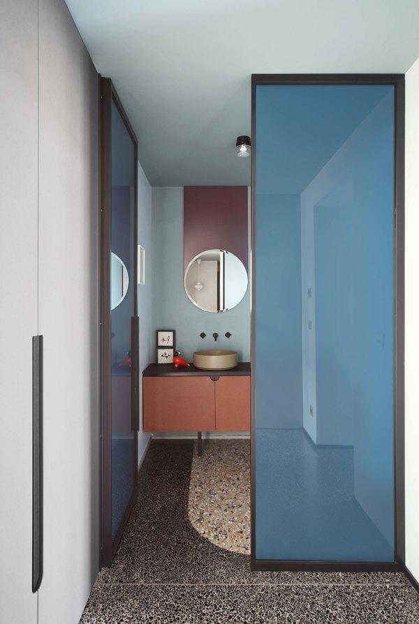 bathroom with soft blue wall, purple lines on the wall on the back of the mirror, wooden vanity, dark brown top, golden sink, stone tiles, blue glass door