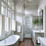 Bathroom, Wooden Floor, White Wooden Planks On The Wall, Thin Chandelier, White Pendant, Light Grey Cabinet With Marble Top, Grey Tub With White Inside, White Curtain