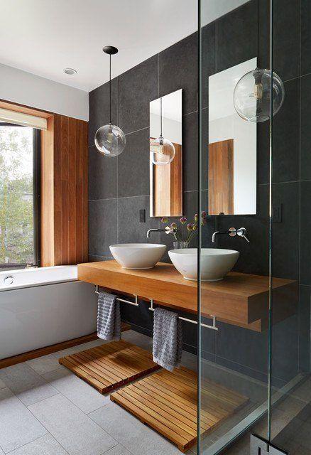 bathroom, wooden vanity with white sink, towel handler under, wooden footing, grey tub, wooden wall, black tiles backsplash, clear bulbs pendants