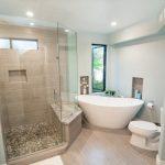 Beachy Bathroom Beige Wall Tile Windows Toilet Beige Floor Mosaic Shower Floor Tile Built In Bench Glass Shower Door Acrylic Freestanding Tub White Vanity