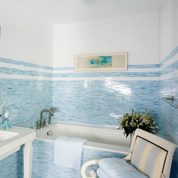 beachy bathroom black mosaic wall tiles white wall artwork built in bathtub white freestanding sink white chairs towel holder chrom tub filler towel