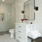 Beachy Bathroom Glass Shower Wall Built In Shelves Mosaic Floor Tile White Wall Black Wall Sconces Wall Mirror White Vanity White Sink Wooden Bench Towels
