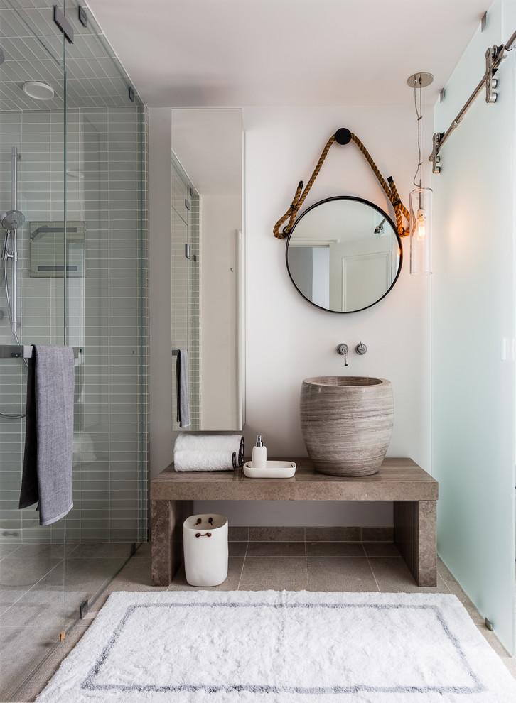 beachy bathroom round wall mirror glass shower door towel holder white bathroom rug limestone floor wooden bench sink bowl mirrored cabinet frosted glass sliding door