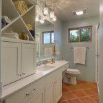 Beachy Bathroom Terra Cotta Floor Tile Towel Holder Window Glass Showerdoors White Cabinet Glass Wall Sconce Toilet Sink Wall Mirror