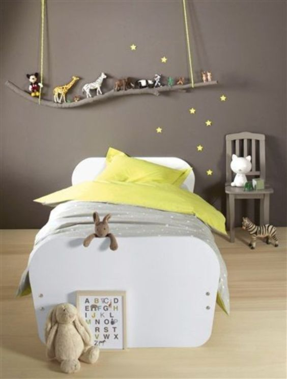 bedroom with light wooden floor, white bed platform, grey green bedding, grey wall branch shelves with animals