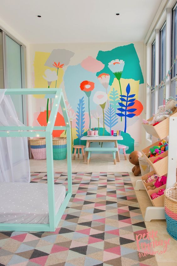 bedroom with white floor, soft colored flowers wallpaper, soft colored children's table and chairs, shelves, green bed platform