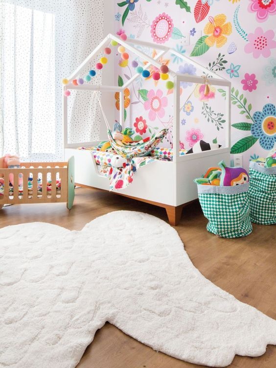 bedroom with wooden floor, white wings rug, white bed platform, green toys basket, wooden box, colorful flowers wall