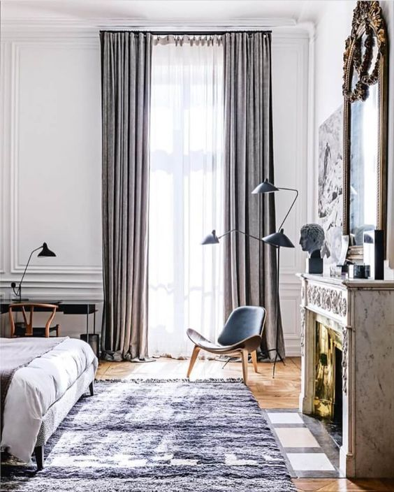 bedroom, wooden floor, tall glass window, white wall, white ceiling, modern study table and chair, modern floor lamp, fireplace, old golden mirror, bed