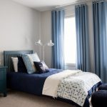 Blue And Gray Bedroom Gray Walls Blue Bedding Blue Wooden Headboard White Standing Lamp Blue Curtains Windows Round Wall Mirror Black Ottoman Nightstand
