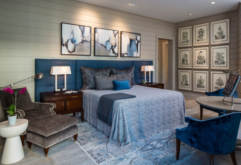 blue and gray bedroom grey walls blue headboard artwork white table lamps nightstands blue bedding blue rug blue chairs side tables