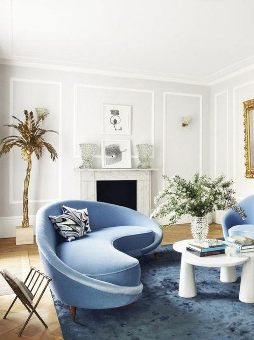 blue modern curvy sofa with continued back and arm rest blue rug, white coffee table, off white room