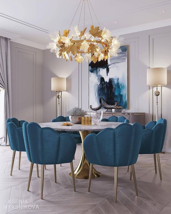 blue shell chairs with metal legs on dining room with marble round table, wooden chevron floor, golden chandelier, floor lamps, white wall