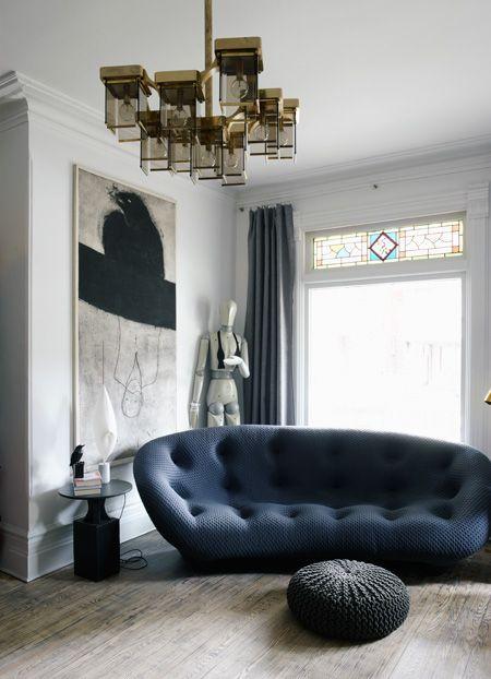 blue tufted curvy sofa, ottoman, wooden floor, pendant, white wall, window