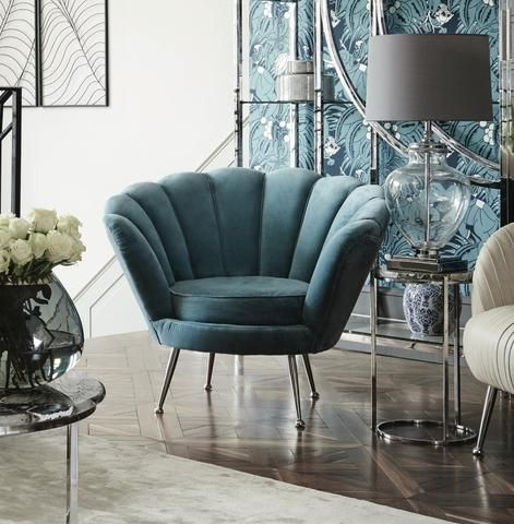 blue velvet shells chair with metal legs, wooden floor, wide table wth metal frame, off white rug, blue wallpaper, grey table lamp