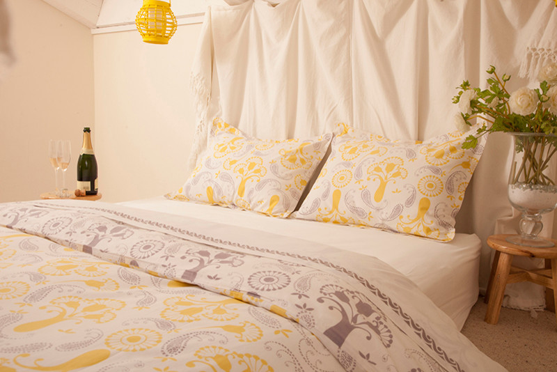 bohemian duvet cover silk fabric wooden stool glass flower vase white walls yellow pendant lamp wooden side table pillows