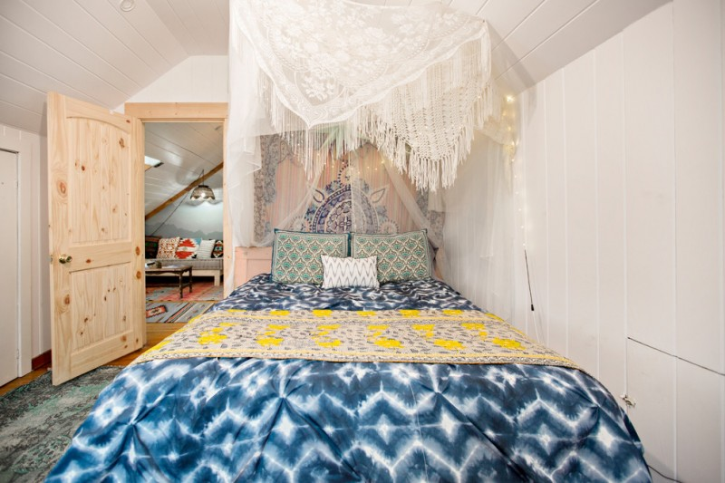 bohemian duvet cover white drapery colorful pillows bohemian fabric wall decor wooden door white walls headboard green rug white sloped ceiling