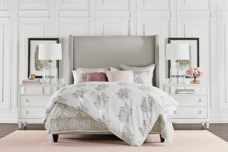 bohemian duvet cover white walls frames glass table lamps white shades white nightstands white bedding pink rug wooden floor beige headboard drawers