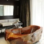 Brown Raw Wooden Look Bath Tub, White Marble, Black Shelves With White Marble Sink And Backsplash, Mirror,