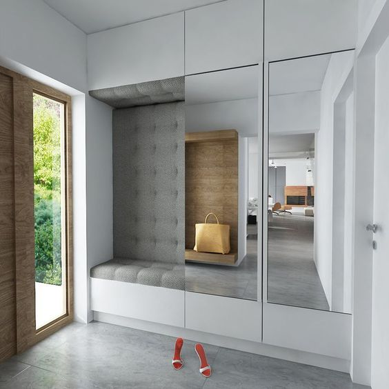 built in cupboard with large mirror door, seating nok with grey cushion on the seating, wall, and ceiling