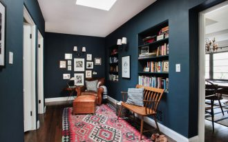 built in shelves on the wall in dark blue, brown leather lounge, wooden bench, white sconces