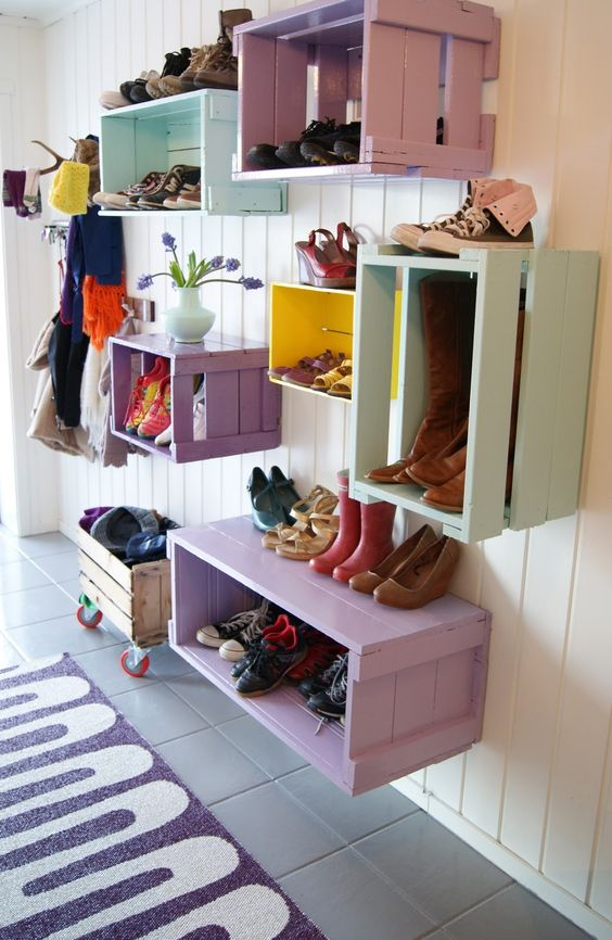 colorful wooden crate used for shoe rack on the hallway with white wooden wall, grey floor tiles, rug
