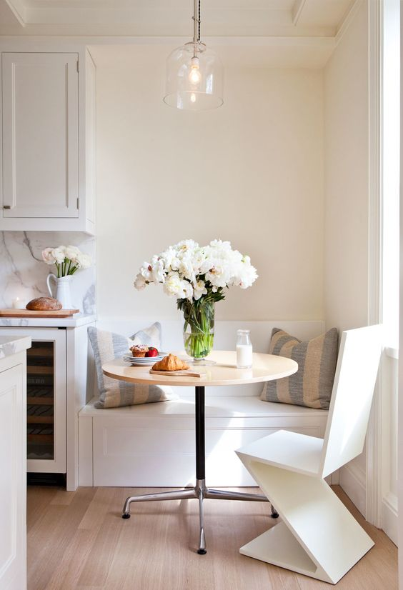 corner breakfast bar, white bench along the wall, round table, modern chair, glass pendant