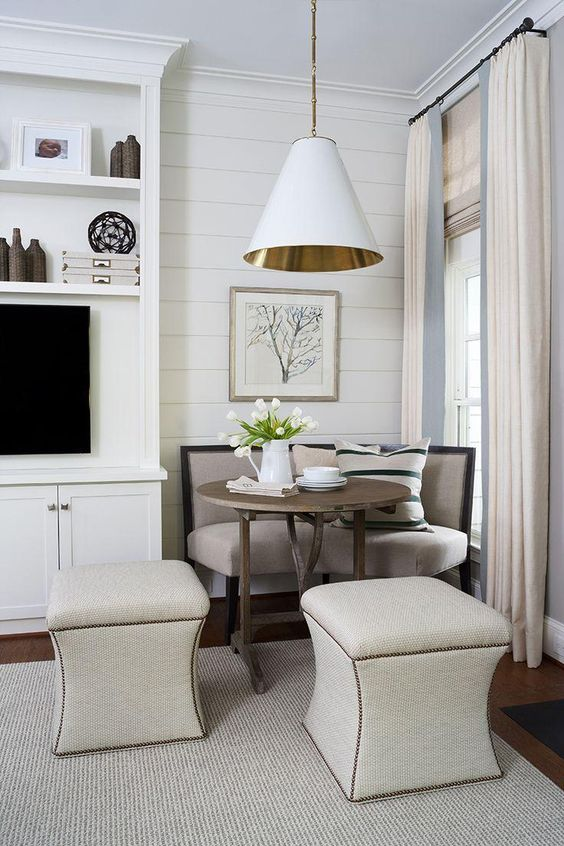 corner dining nook, corner sofa with legs, white stools, round table, whtie cone pendant, white plank wall, white curtain, white entertainment cabinet, wooden floor