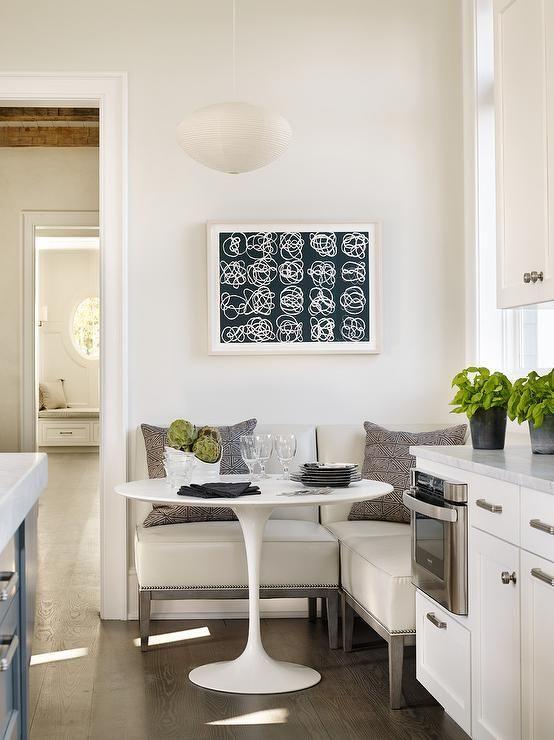 corner dining nook, white corner sofa, round table, white pendants