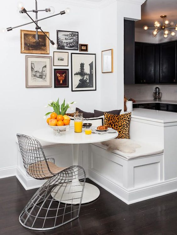 corner dining nook with white built in bench, curvy metal chair, white round table