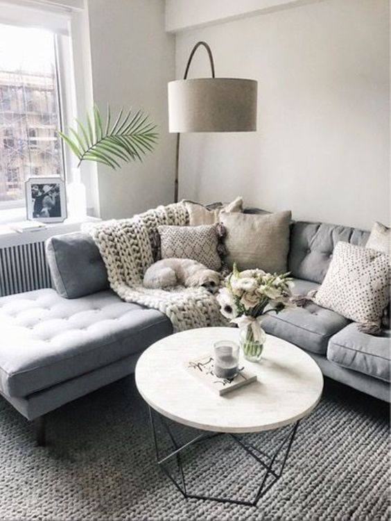 corner sofa with tufted seating adn back, longue side, pillows, white round coffee table