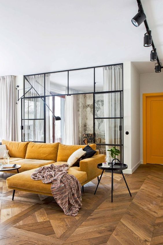 corner yellow sofa in the living room, wooden floor, glass partition, round side table, round coffee table