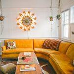 Curvy Corner Yellow Sofa, Rug, White Wall, Hanging Plants, Rectangular Wooden Coffee Table