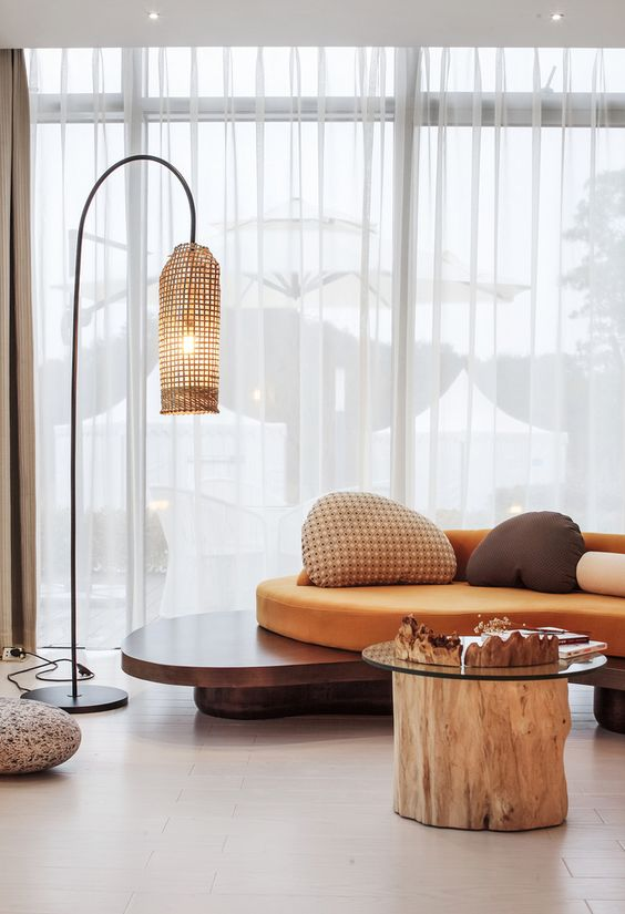 curvy wooden bench with orange seating and back, pillows, wooden floor, rattan floor lamp, wooden coffee table