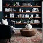 Dark Brown Wooden Floating Shelves, Dark Green Wall, Black Sofa, Round Wooden Coffee Table, Black Sconces