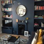 Dark Floating Bookcase On Two Sides Of Indented Wall Iwth Fireplace, Wooden Floor, Rug, Black Coffee Table, Grey Sofa