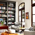 Dark Tall Bookcase, Grey Chairs, White Wall, Tall Windows Brown Wooden Framed, Beige Floor, Rug, Round Coffee Table